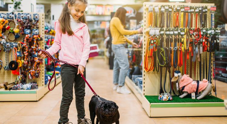 Menina passeando com cachorrinho em pet shop